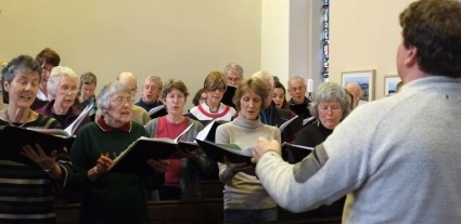conductor rehearsing the choir 'in the pews' in Jesmond United reformed church